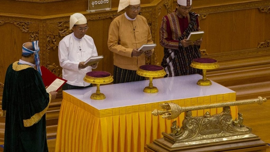 Htin Kyaw, second right, takes oaths as Myanmar's new president during a sworn-in ceremony in Myanmar's parliament in Naypyitaw, Myanmar, Wednesday, March 30, 2016. Htin Kyaw, a confidante of Nobel laureate Aung San Suu Kyi, was sworn in Wednesday as Myanmar's president. (AP Photo/Gemunu Amarasinghe)