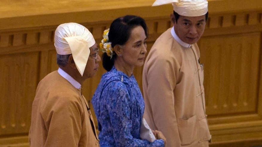 Htin Kyaw, left, newly elected president of Myanmar walks with National League for Democracy party leader Aung San Suu Kyi, center, to attend a sworn-in ceremony at parliament in Naypyitaw, Myanmar, Wednesday, March 30, 2016. Htin Kyaw, a trusted friend of Nobel laureate Suu Kyi, took over as Myanmar's president Wednesday, taking a momentous step in the country's long-drawn transition toward democracy after more than a half-century of direct and indirect military rule. (AP Photo/Gemunu Amarasinghe)
