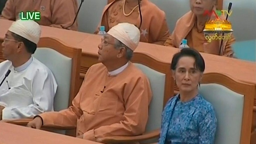 In this image taken from video, Htin Kyaw, center, and National League for Democracy party leader Aung San Suu Kyi, right, attend the presidential swearing in ceremony at parliament in Naypyitaw, Myanmar Wednesday, March 30, 2016. Htin Kyaw, a trusted friend of Nobel laureate Suu Kyi, took over as Myanmar's president Wednesday, taking a momentous step in the country's long-drawn transition toward democracy after more than a half-century of direct and indirect military rule. (MRTV via AP Video) MYANMAR OUT, TV OUT