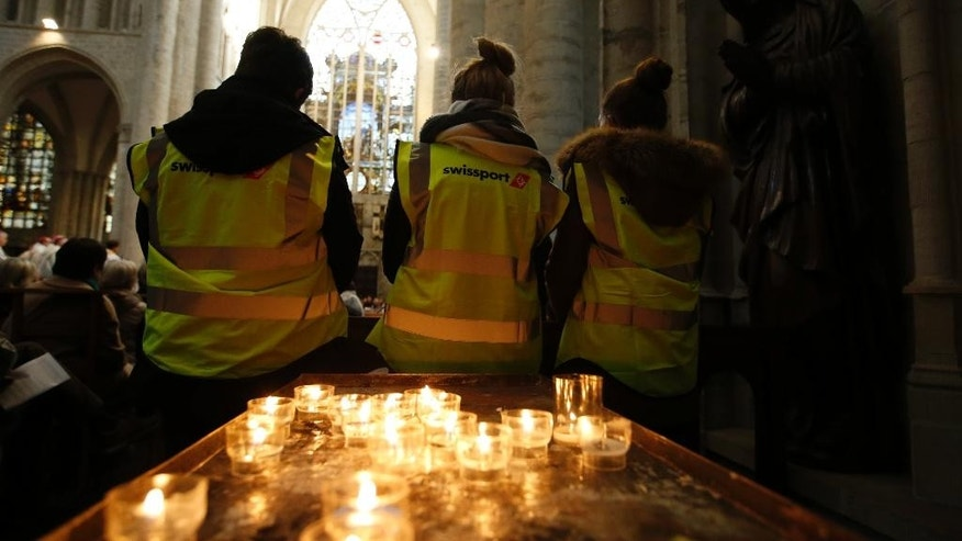 Three Brussels airport workers attend an ecumenical service for the victims of the Brussels bomb attacks at the Cathedral of St. Michael and St. Gudula in Brussels, Monday, March, 28, 2016.  The Belgian Health Minister Minister Maggie De Block says four of those wounded in the suicide bombings last week have died in the hospital, bringing the number of victims of the bombings to 35. (AP Photo/Alastair Grant)