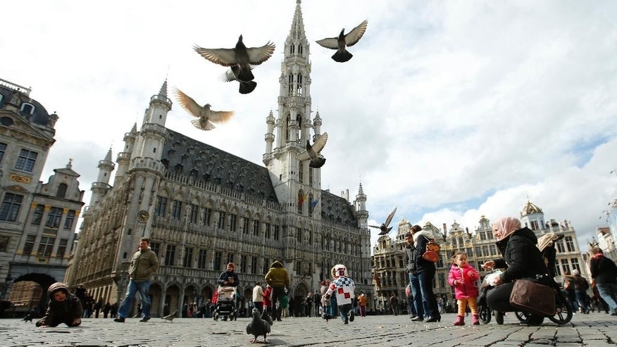 Pigeons  take flight as tourists feed them in the Grand Place in Brussels, Monday, March, 28, 2016. The Belgian health minister says four of those wounded in the suicide bombings last week have died in the hospital.(AP Photo/Alastair Grant)