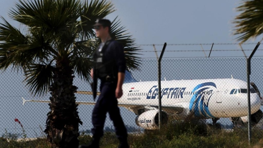 A police officer patrols outside the airport as an hijacked aircraft of EgyptAir is seen after landing at Larnaca Airport in Cyprus Tuesday, March 29, 2016. The EgyptAir plane was hijacked on Tuesday while flying from the Egyptian Mediterranean coastal city of Alexandria to the capital, Cairo, and later landed in Cyprus where some of the women and children were allowed to get off the aircraft, according to Egyptian and Cypriot officials. (AP Photo/Petros Karadjias)