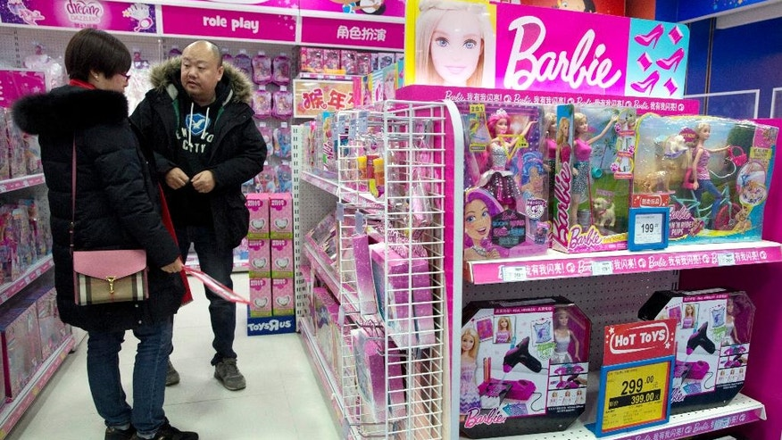 In this Saturday, Feb. 27, 2016, photo, a man and woman look at Barbie dolls at a store in Beijing, China. Sophisticated cyber-thieves tricked Mattel Inc., the Los-Angeles based maker of Barbie dolls, into sending over $3 million to a Chinese bank account they controlled. Mattel's millions were swept up in a tide of dirty money that passes through China, which Western police are only beginning to understand. (AP Photo/Ng Han Guan)