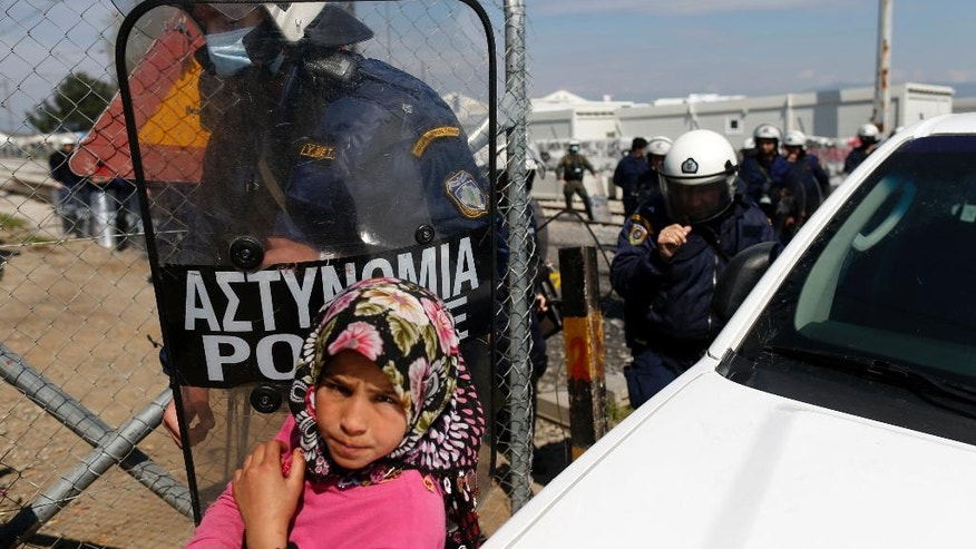 Greek police officers leave after a protest demanding the opening of the border between Greece and Macedonia in the northern Greek border station of Idomeni, Greece, Tuesday, March 29, 2016. More than 15,000 people - nearly a third of the total stranded in Greece - are refusing to move to government-built shelters around the country, and remain at the border with Macedonia and at the port of Piraeus, near Athens. (AP Photo/Darko Vojinovic)