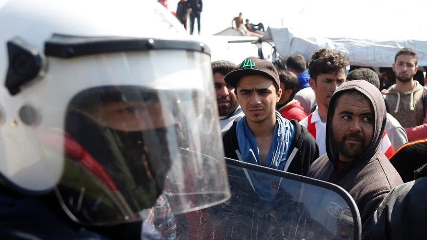Migrants stand in front of Greek police officers during a protest demanding the opening of the border between Greece and Macedonia in the northern Greek border station of Idomeni, Greece, Tuesday, March 29, 2016. More than 15,000 people - nearly a third of the total stranded in Greece - are refusing to move to government-built shelters around the country, and remain at the border with Macedonia and at the port of Piraeus, near Athens. (AP Photo/Darko Vojinovic)