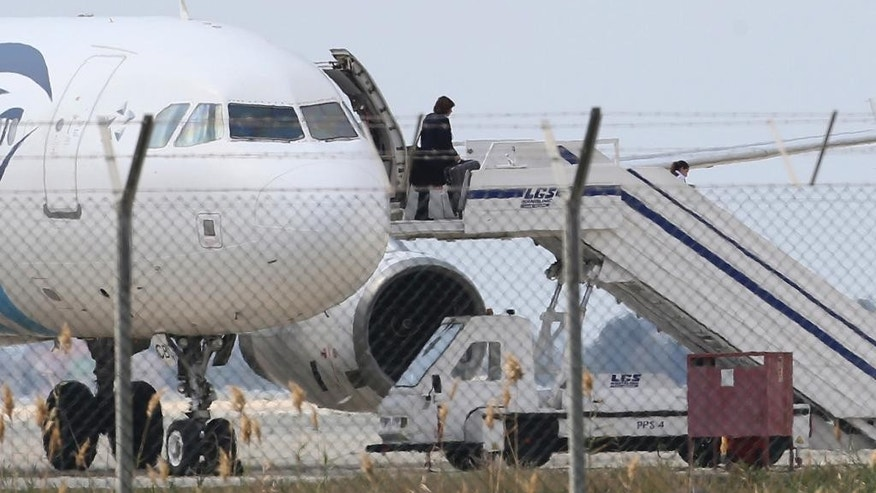 A passenger leaves a hijacked EgyptAir aircraft after landing at Larnaca Airport in Cyprus Tuesday, March 29, 2016. An Egyptian man hijacked the EgyptAir plane Tuesday and forced it to land in Cyprus, where all but several foreign passengers and the crew were eventually allowed to get off, Egyptian and Cypriot officials said. (AP Photo/Petros Karadjias)