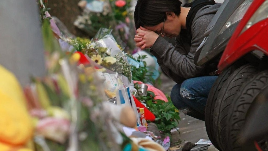 A woman prays in front of a makeshift memorial offered with flowers and stuffed animals for a girl who was attacked to death Monday by a knife-wielding assailant outside a subway station in Taipei, Taiwan, Tuesday, March 29, 2016. A transit police officer was stabbed in the head Tuesday a day after a young girl was decapitated in apparently random knife attacks in Taiwan's capital early Monday. (AP Photo/Chiang Ying-ying)