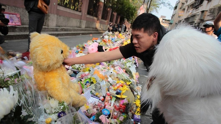 A man places a stuffed animal to a makeshift memorial offered with flowers for a girl who was attacked to death Monday by a knife-wielding assailant outside a subway station in Taipei, Taiwan, Tuesday, March 29, 2016. A transit police officer was stabbed in the head Tuesday a day after a 3-year-old girl was decapitated in apparently random knife attacks in Taiwan's capital early Monday. (AP Photo/Chiang Ying-ying)