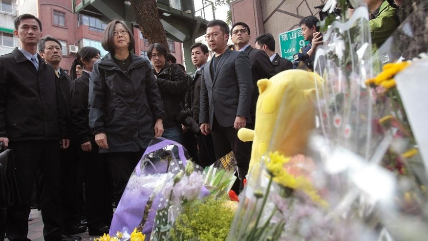 Taiwan's President-elect Tsai Ing-wen, second left, visits a makeshift memorial for a girl who was attacked to death Monday by a knife-wielding assailant outside a subway station in Taipei, Taiwan, Tuesday, March 29, 2016. A transit police officer was stabbed in the head at another subway station in the city Tuesday, a day after a 3-year-old girl was decapitated in apparently random knife attacks in Taiwan's capital. (AP Photo/Chiang Ying-ying)