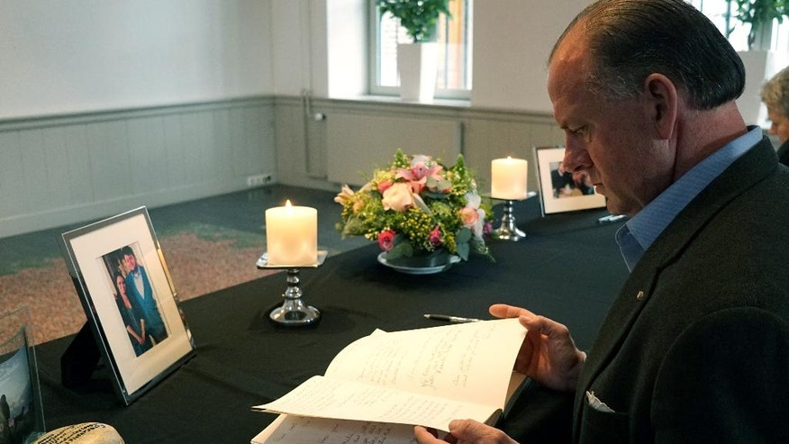 The former U.S ambassador to Denmark, James P. Cain, reads messages of condolences in memory of his son-in-law Alexander Pinczowski and his sister Sascha Pinczowski, in Maastricht, Netherlands, Tuesday, March 29, 2016. The two siblings were Dutch nationals who lived in the U.S. and were headed home to the United States when a bomb exploded at the Brussels airport Tuesday morning. (AP Photo/David Keyton)