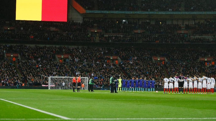 The Belgian flag is seen on a screen as players of the Dutch, in blue, and England soccer squads observe a minute of silence to commemorate the victims of the Brussels attacks prior during the international friendly soccer match between England and The Netherlands at Wembley stadium in London, Tuesday, March 29, 2016. (AP Photo/Kirsty Wigglesworth)
