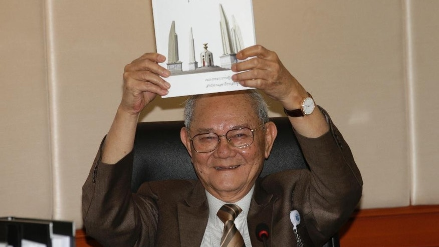 Chairman of the Constitution Drafting Commission Meechai Ruchupan holds the draft of new constitution during a press conference at the Parliament in Bangkok, Thailand, Tuesday, March 29, 2016. The proposed constitution, unveiled Tuesday, will be put to a referendum in August, followed by elections that junta chief Prayuth Chan-ocha has promised for 2017.(AP Photo/Sakchai Lalit)