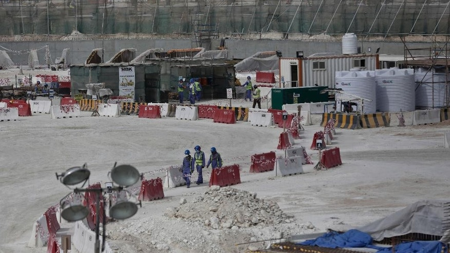 FILE - In this May 4, 2015, file photo taken during a government organized media tour, foreign workers walk between safety barricades at the site of the pitch of the Al-Wakra Stadium that is under construction for the 2022 World Cup in Doha, Qatar. Migrant laborers faced abuse that in some cases amounted to forced labor while working on a stadium that will host soccer matches for the 2022 World Cup in Qatar, a new report released by Amnesty International alleged Thursday, March 31, 2016. (AP Photo/Maya Alleruzzo, File)