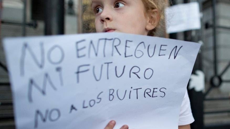 "A young demonstrator holds a sign that says in Spanish: ""Don't turn over my future. No to the vultures"" during a protest against a new debt payment deal being debated by lawmakers, outside Congress in Buenos Aires, Argentina, Wednesday, March 30, 2016. Argentina's Senate is debating the deal with a group of creditors in the U.S. that would put an end to a years-long dispute that has kept the South American nation on the margins of international credit markets. (AP Photo/Natacha Pisarenko)"