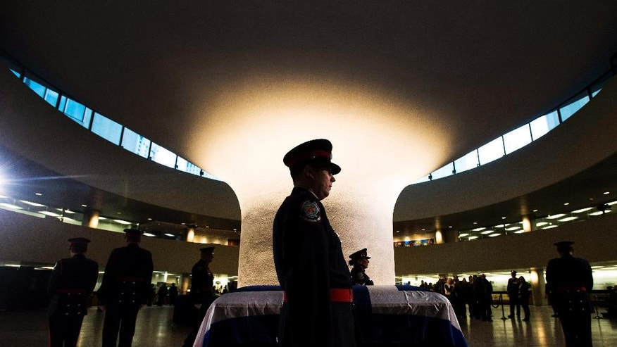 An honor guard stands by former Toronto Mayor Rob Ford's casket at city hall on Monday, March 28, 2016, in Toronto. Ford died of cancer at the age of 46. (Nathan Denette/The Canadian Press via AP) MANDATORY CREDIT