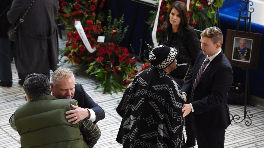 Doug Ford, second from left, brother of former Toronto mayor Rob Ford, and nephew Mike Ford, right, greet well wishers at city hall on Tuesday, March 29, 2016 in Toronto. Rob Ford died of cancer on March 22. (Frank Gunn/The Canadian Press via AP) MANDATORY CREDIT