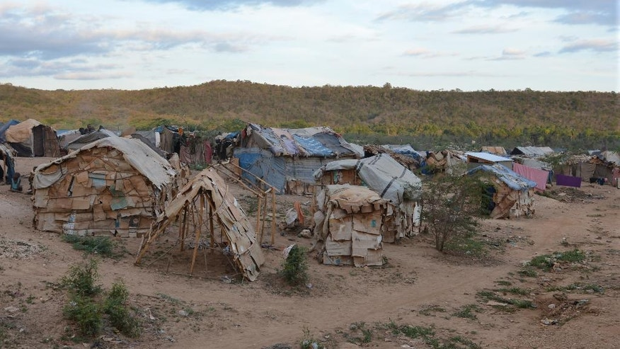 In this March 21, 2015 photo, makeshift tents of flattened cardboard boxes, bedsheets and sticks stand at a borderland encampment outside the southeast Haitian town of Anse-a-Pitres. The encampment is filled with people who either fled or were forcibly removed from the neighboring Dominican Republic amid an immigration crackdown. Within a month, authorities hope to move nearly 2,400 people in a half-dozen encampments by providing enough money for them to rent homes for a year in nearby towns. (AP Photo/David McFadden)