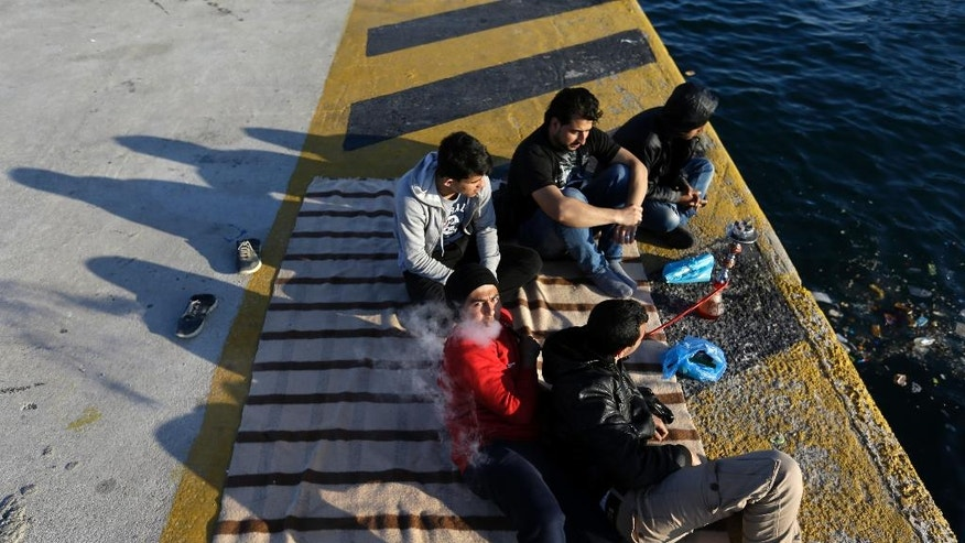 Syrian refugees smoke hookahs at the Athens' port of Piraeus on Tuesday, March 29, 2016. About 5,500 refugees and migrants are refusing to move to government-built shelters around the country, and remain at the passenger terminal buildings, a warehouse and their tents at the biggest port of Greece. (AP Photo/Thanassis Stavrakis)