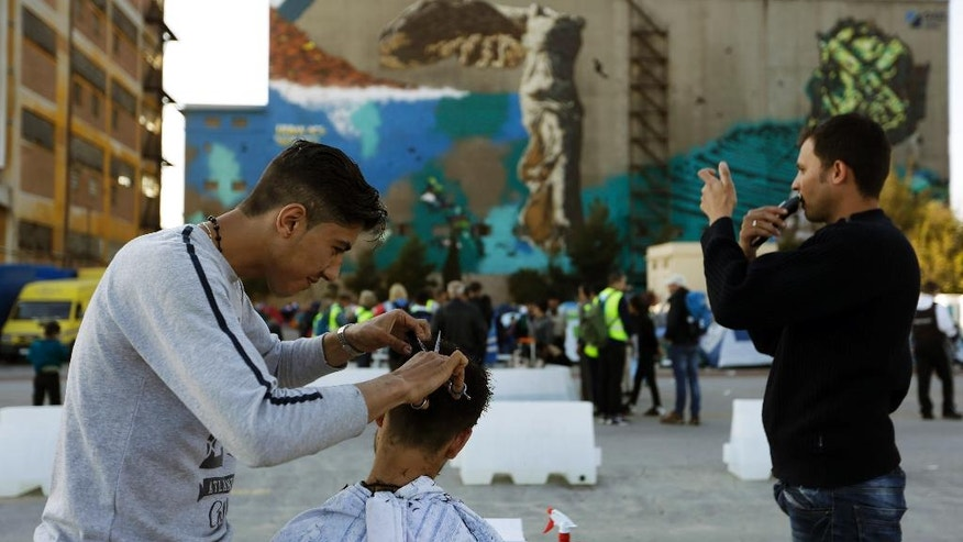A migrant barber cuts the hair of a man as another one shaves himself at the Athens' port of Piraeus on Tuesday, March 29, 2016. About 5,500 refugees and migrants are refusing to move to government-built shelters around the country, and remain at the passenger terminal buildings, a warehouse and their tents at the biggest port of Greece. (AP Photo/Thanassis Stavrakis)