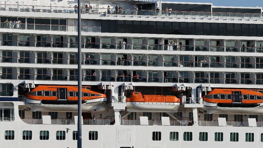 Refugees and migrants wave to the passengers of a Norwegian cruise ship as they depart from the Athens' port of Piraeus on Tuesday, March 29, 2016. About 5,500 people are refusing to move to government-built shelters around the country, and remain at the passenger terminal buildings, a warehouse and their tents at the biggest port of Greece. (AP Photo/Thanassis Stavrakis)