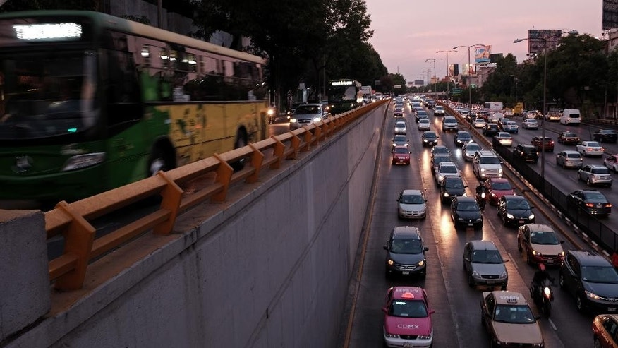 """Traffic advances slowly as the day ends in Mexico City, Wednesday, March 30, 2016. Metropolitan authorities temporarily ordered all cars to remain idle one day a week in response to this city's worst air-quality crisis in over a decade. Until now vehicles have been exempt from Mexico City's """"no circulation"""" rules if owners obtain a sticker from a smog-check center certifying them as lower-emission. Vehicles will also be forced from the roads one Saturday a month. (AP Photo/Dario Lopez-Mills)"""