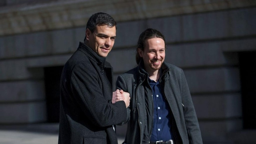Spain's Socialist Party leader Pedro Sanchez, left, shakes hands with Podemos Party leader Pablo Iglesias for the media as they arrive to the Spanish Parliament before their meeting in Madrid, Wednesday, March 30, 2016. (AP Photo/Francisco Seco)
