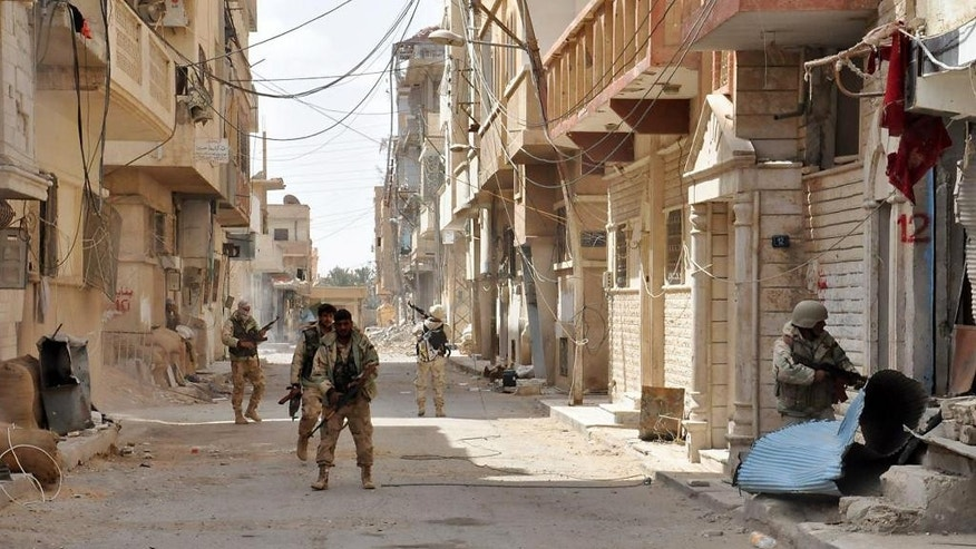 This photo released on Sunday March 27, 2016, by the Syrian official news agency SANA, Syrian government soldiers patrol a street in the ancient city of Palmyra, central Syria. The amount of destruction found inside the archaeological area in the historic town  was similar to what experts have expected but the shock came Monday from inside the local museum where the extremists have caused wide damage demolishing invaluable statues that were torn to pieces. (SANA via AP)