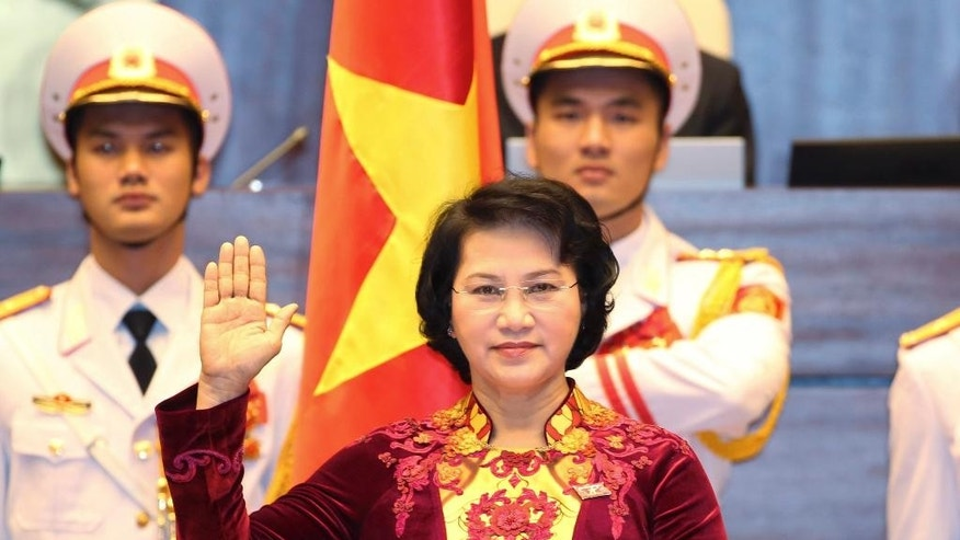 Nguyen Thi Kim Ngan takes the oath of office after being elected as chairwoman of the National Assembly in Hanoi, Vietnam Thursday, March 31, 2016. Vietnam's parliament on Thursday elected Ngan as its chairwoman, making her the first woman to lead the Communist-dominated legislature. (Thong Nhat/Vietnam News Agency via AP)