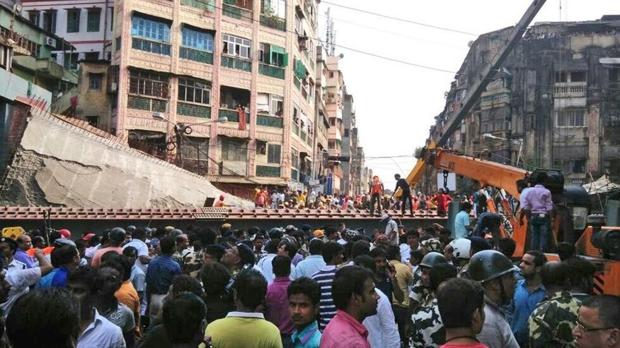 People watch as locals and rescue workers clear the rubbles of a partially collapsed overpass in Kolkata, Thursday, March 31, 2016. At least dozens have been injured and few were killed when a portion of an overpass under construction collapses in a congested area in the eastern Indian city of Kolkata. (AP Photo/Bikas Das)
