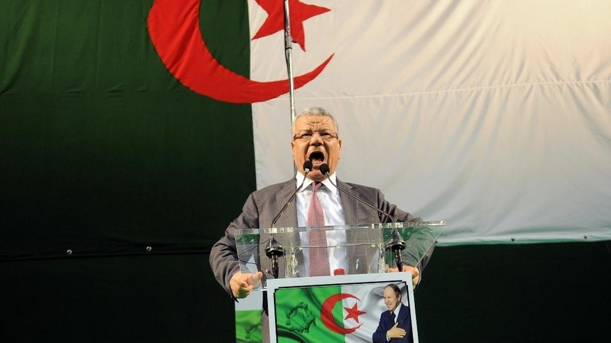 In this photo dated Wednesday, March 30, 2016 governing FLN party chief Amar Saadani delivers his speech during a rally held in Algiers, Algeria. Political tensions are bubbling between Algeria's governing party and the opposition as threats of Islamic extremist violence and low oil prices that are pummeling the energy-dependent economy. Algerian flag is seen on background. (AP Photo/Sidali Djarboud)