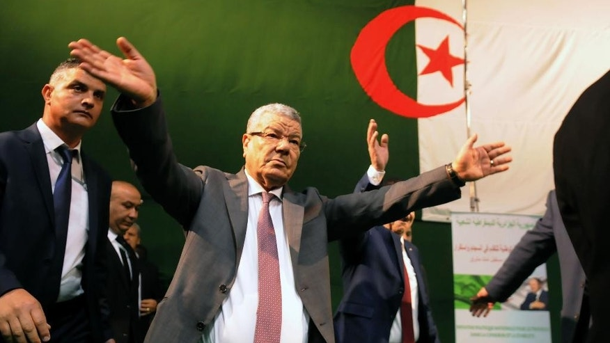 In this photo dated Wednesday, March 30, 2016 governing FLN party chief Amar Saadani waves to supporters during a rally held in Algiers, Algeria. Political tensions are bubbling between Algeria's governing party and the opposition as threats of Islamic extremist violence and low oil prices that are pummeling the energy-dependent economy. Algerian flag is seen on the background. (AP Photo/Sidali Djarboud)