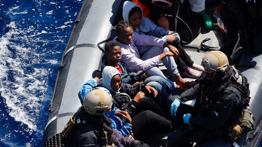 In this March 29, 2016 picture,  rescued migrants sit in a German Navy boat besides Finish Special Forces,  prior to board the German combat supply ship 'Frankfurt am Main' during EUNAVFOR MED Operation Sophia in the Mediterranean Sea off the coast of Libya. (AP Photo/Matthias Schrader)