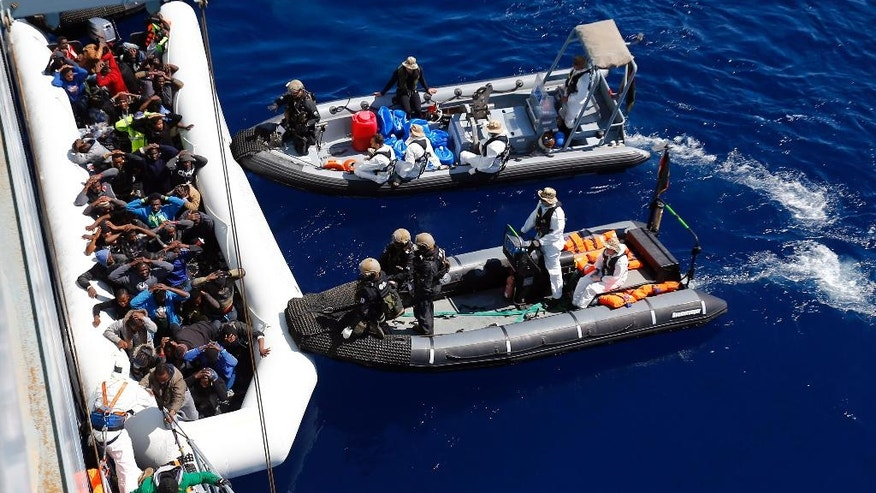 In this March 29, 2016  picture German Navy sailors and  Special Forces from Finland  help migrants to board the German combat supply ship 'Frankfurt am Main' during  EU NAVFOR MED Operation Sophia in the Mediterranean Sea off the coast of Libya.  (AP Photo/Matthias Schrader)