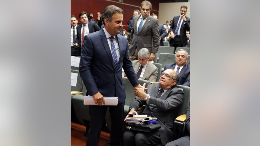 "Brazilian Senator Aecio Neves, center left, shakes hands with Brazil'z Supreme Court Justice Gilmar Mendes at a legal conference in Lisbon, Thursday, March 31 2016. Neves, the leader of the Social Democracy Party who narrowly lost to Dilma Rousseff in a 2014 presidential runoff, says the Brazilian government ""has lost its legitimacy, the ability to run the country."" Besides Neves and Mendes, the conference included other participants seen as opponents of Rousseff.(AP Photo/Armando Franca)"