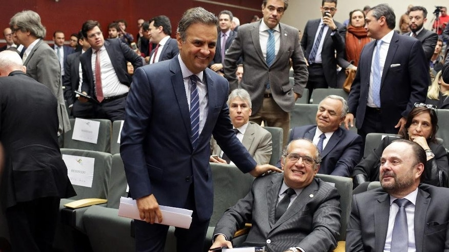 "Brazilian Senator Aecio Neves, center left, pats the shoulder of Brazil's Supreme Court Justice Gilmar Mendes at a legal conference in Lisbon, Thursday, March 31, 2016. Neves, the leader of the Social Democracy Party who narrowly lost to Dilma Rousseff in a 2014 presidential runoff, says the Brazilian government ""has lost its legitimacy, the ability to run the country."" Besides Neves and Mendes, the conference included other participants seen as opponents of Rousseff.(AP Photo/Armando Franca)"
