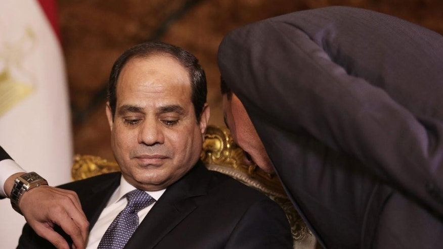 FILE - In this Saturday, Sept. 20, 2015 file photo, Egyptian President Abdel-Fattah el-Sissi confers with an aide before an interview with The Associated Press at the presidential palace in Cairo. Nearly three years into a heavy crackdown overseen by President Abdel-Fattah el-Sissi, allegations of human rights abuses including killings, torture and secret detentions are starting to bring an international backlash from the Egyptian leader's allies.(AP Photo/Maya Alleruzzo, File)