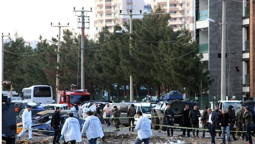 Security and forensic officers work at the site after an explosion caused by a bomb-laden car targeting police in the mainly Kurdish city of Diyarbakir, Turkey, Thursday, March 31, 2016, Turkish news agencies reported.  The explosives detonated as a vehicle carrying special forces and riot police passed by, causing many deaths and injuries.(AP Photo/Mahmut Bozarslan)