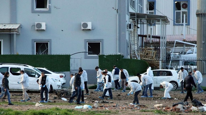 Security and forensic officials work at the site after an explosion caused by a bomb-laden car targeting police in the mainly Kurdish city of Diyarbakir, Turkey, Thursday, March 31, 2016, Turkish news agencies reported.  The explosives detonated as a vehicle carrying special forces and riot police passed by, causing many deaths and injuries.(AP Photo/Mahmut Bozarslan)