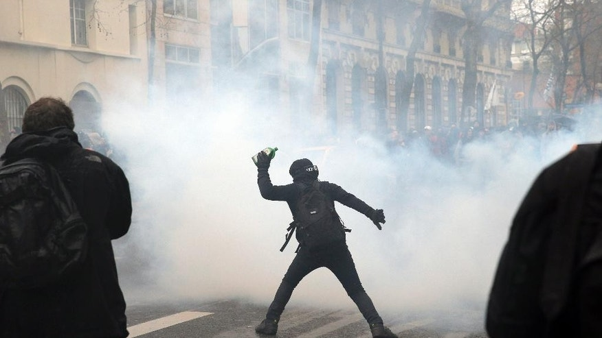 A demonstrator throws a bottle during a protest in Paris, Thursday, March 31, 2016. Student organizations and employee unions have joined to call for protests across France to reject the Socialist government's bill, which they consider as badly damaging hard-fought worker protections. (AP Photo/Christophe Ena)