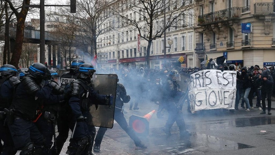 Demonstrators face riot police officers during a protest in Paris, Thursday, March 31, 2016. Student organizations and employee unions have joined to call for protests across France to reject the Socialist government's bill, which they consider as badly damaging hard-fought worker protections. Banner reads: Paris is magic. (AP Photo/Christophe Ena)