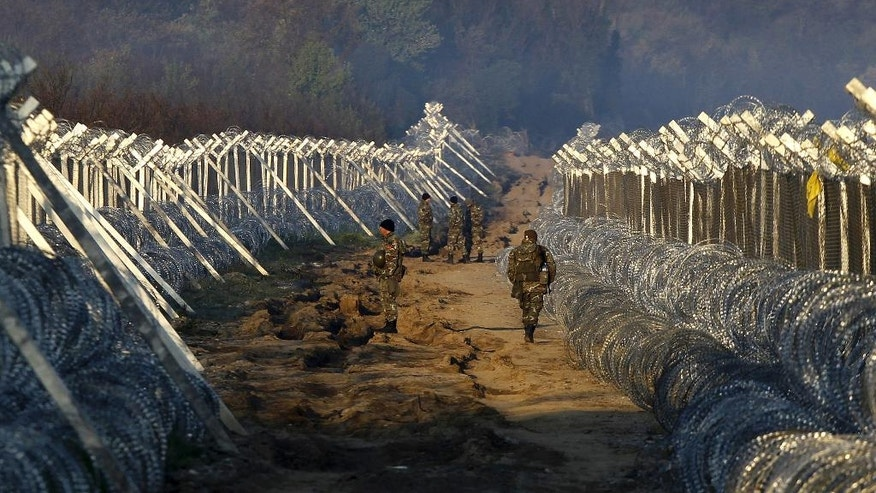 Macedonian Army soldiers patrol between the two-line fence set along the border line between Macedonia and Greece, near southern Macedonian town of Gevgelija, early Thursday, March 31, 2016. More than 50,000 migrants remain stranded in Greece following border restrictions and closures by Austria and Balkan nations. (AP Photo/Boris Grdanoski)