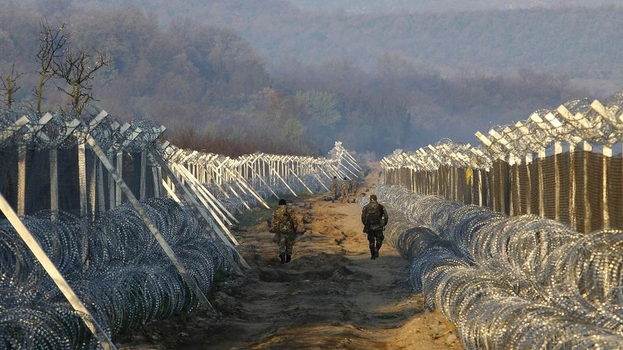 Macedonian Army soldiers patrol between two-line fence, set along the border line between Macedonia and Greece, near southern Macedonian town of Gevgelija, early Thursday, March 31, 2016. More than 50,000 migrants remain stranded in Greece following border restrictions and closures by Austria and Balkan nations. (AP Photo/Boris Grdanoski)