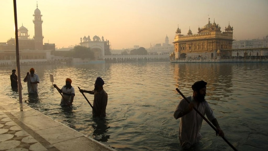 FILE- In this Nov. 17, 2013, file photo, Indian Sikh devotees clean the tank early in the morning at the Golden Temple, on the birth anniversary of Guru Nanak, the first Sikh Guru in Amritsar, India. The chronic air pollution blanketing much of northern India is now threatening the holiest shrine in the Sikh religion, making the once-gleaming walls of the Golden Temple dingy and dull. (AP Photo/Sanjeev Syal, File)
