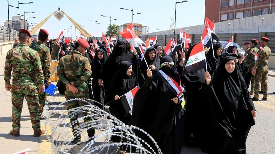 Women rally in front of the fortified Green Zone in solidarity with the sit-in carried out by supporters of Shiite cleric Muqtada al-Sadr in Baghdad, Iraq, Wednesday, March,30, 2016. (AP Photo/Karim Kadim)