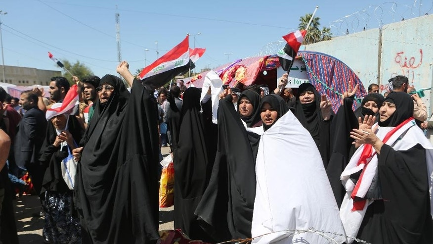 Followers of Shiite cleric Muqtada al-Sadr chant slogans during a sit-in outside the heavily guarded Green Zone in Baghdad, Iraq, Thursday, March 31, 2016. A parliamentary vote on a cabinet re-shuffle comes as al-Sadr followers continue a sit-in, calling for political reform and an end to corruption. On Sunday, al-Sadr ramped up pressure on the government by beginning a sit-in inside the Green Zone, home to key government offices and foreign embassies.(AP Photo/Khalid Mohammed)