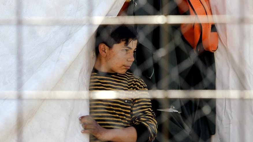 A refugee boy looks on from a tent in a makeshift camp at Idomeni border station on the Greek side of the border with Macedonia, photographed through a fence from the Macedonian side of the border line, Thursday, March 31, 2016. More than 50,000 migrants remain stranded in Greece following border restrictions and closures by Austria and Balkan nations. (AP Photo/Boris Grdanoski)