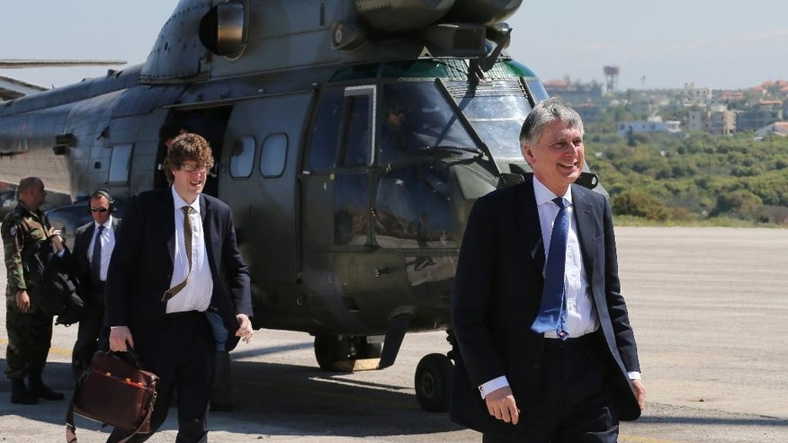 British Foreign Secretary Philip Hammond, center, walks in front a Lebanese army helicopter that carried him from Beirut to an army air base to attend a Lebanese Special Forces drill, in Hamat village, 65 kilometers (40 miles) north of Beirut, Lebanon, Thursday, March 31, 2016. (AP Photo/Hussein Malla)