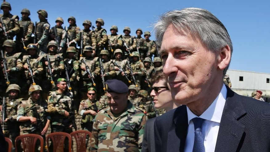 British Foreign Secretary Philip Hammond walks in front of Lebanese army soldiers who trained by British instructors under a UK funded program, after he attended a Special Forces drill at their base, in Hamat Lebanese army air base, 65 kilometers (40 miles) north of Beirut, Lebanon, Thursday, March 31, 2016. (AP Photo/Hussein Malla)