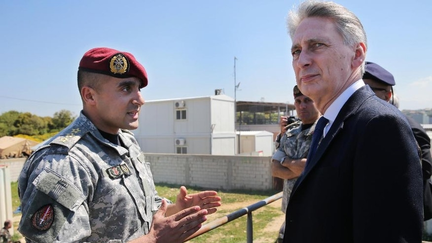 British Foreign Secretary Philip Hammond, right, listens to a Lebanese special forces officer, left, as he attends a drill for Lebanese army soldiers who trained by British instructors under a UK funded program, in Hamat Lebanese army air base, 65 kilometers (40 miles) north of Beirut, Lebanon, Thursday, March 31, 2016. (AP Photo/Hussein Malla)