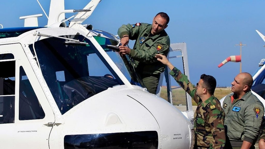 Lebanese army pilots inspect a military Huey II helicopter during a ceremony at the Rafik Hariri International Airport in Beirut, Lebanon, Thursday, March 31, 2016. The United states has given Lebanon three military Huey II helicopters to help the country's armed forces in their battle against extremists near the border with Syria. (AP Photo/Bilal Hussein)